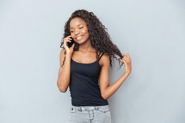 Glimlachende vrouw die aan de telefoon praat over grijze muur
