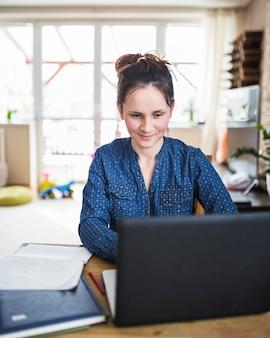 Glimlachende vrouw die aan laptop thuis werkt