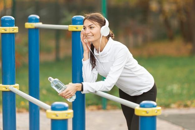 Glimlachende vrouw die aan muziek luistert en een fles water houdt