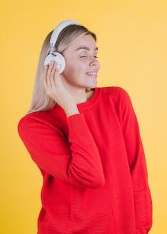 Glimlachende vrouw die aan muziek luistert