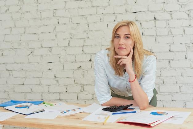 Glimlachende vrouw die alleen in een modern kantoor werkt en naar de camera kijkt. grafieken en papieren liggen op tafel.