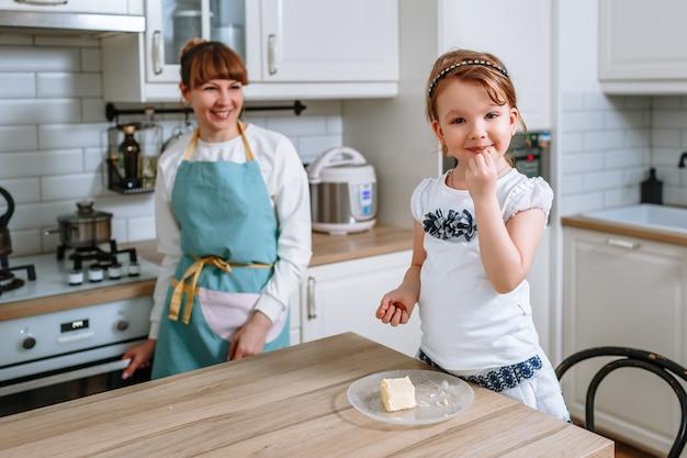 Glimlachende vrouw die amandelen eet. de moeder kijkt naar haar dochter en lacht