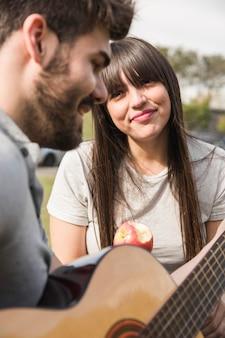 Glimlachende vrouw die appel eet die de mens het spelen gitaar bekijkt