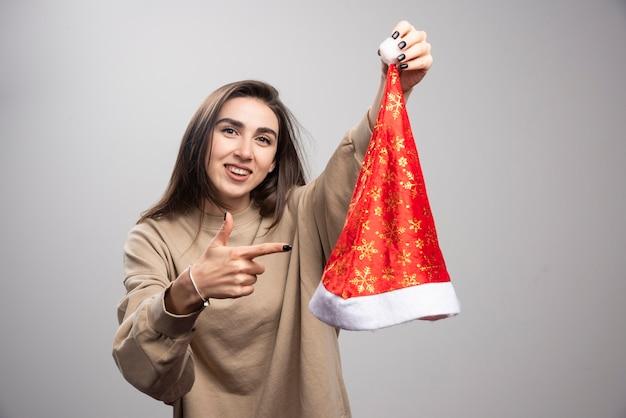 Glimlachende vrouw die bij de hoed van de kerstman op een grijze achtergrond toont.