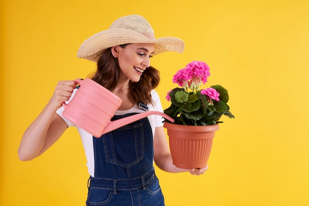 Glimlachende vrouw die bloemen in bloempot water geeft