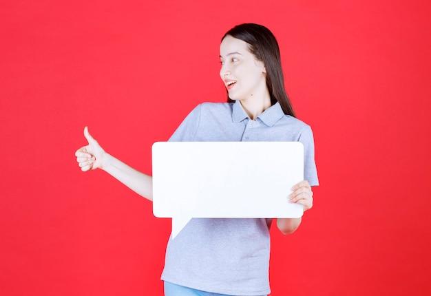 Glimlachende vrouw die bord vasthoudt en duim omhoog gebaart
