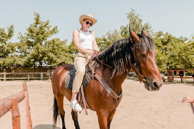 Glimlachende vrouw die bruin paard berijden op een boerderij