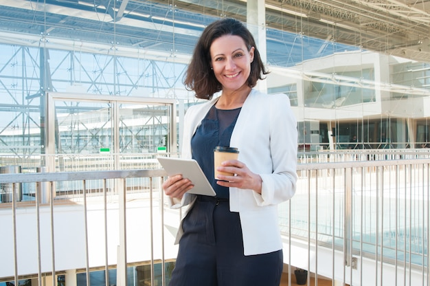 Glimlachende vrouw die camera bekijkt, die tablet, meeneemkoffie houdt