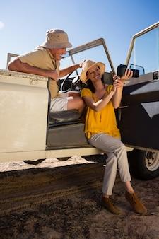 Glimlachende vrouw die camera toont aan de mens in voertuig