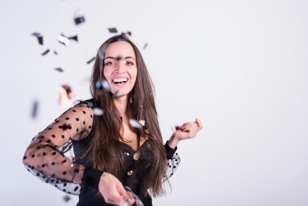 Glimlachende vrouw die confettien werpt