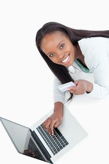 Glimlachende vrouw die creditcardinformatie ingaat