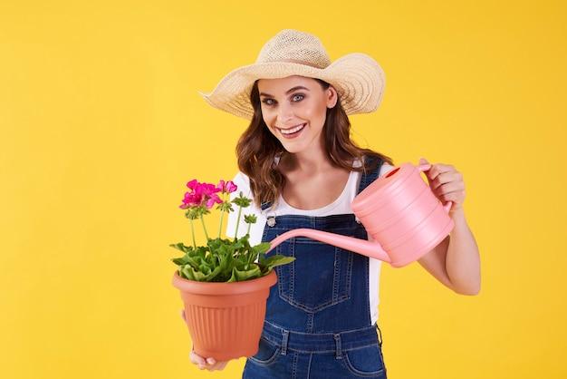 Glimlachende vrouw die de bloem in het studioschot water geeft