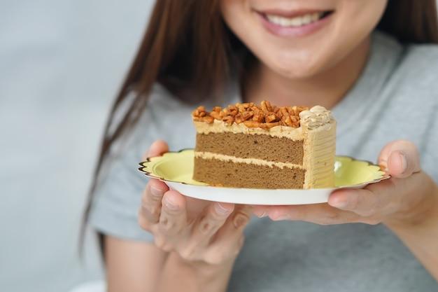 Glimlachende vrouw die de cake bekijkt die zij vasthoudt