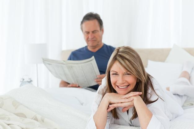 Glimlachende vrouw die de camera bekijkt terwijl haar echtgenoot leest