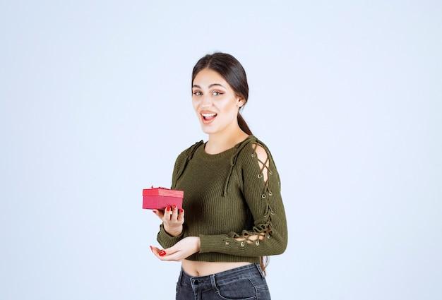 Glimlachende vrouw die de doos van de gift houdt en camera op witte achtergrond bekijkt.