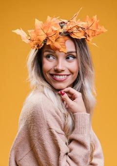 Glimlachende vrouw die de droge tiara dragen van esdoornbladeren die zich tegen gele muur bevinden weg kijkend