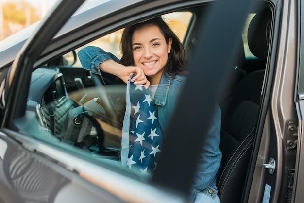 Glimlachende vrouw die de grote vlag van de vs in auto houdt
