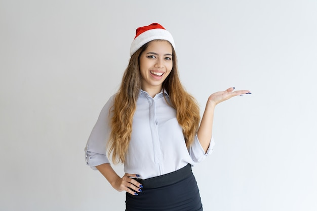 Glimlachende vrouw die de hoed van de kerstman draagt en product voorstelt