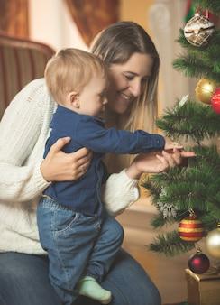 Glimlachende vrouw die de kerstboom versiert met haar zoontje van 10 maanden