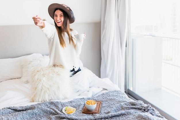 Glimlachende vrouw die de ontbijtzitting op het bed aanbieden