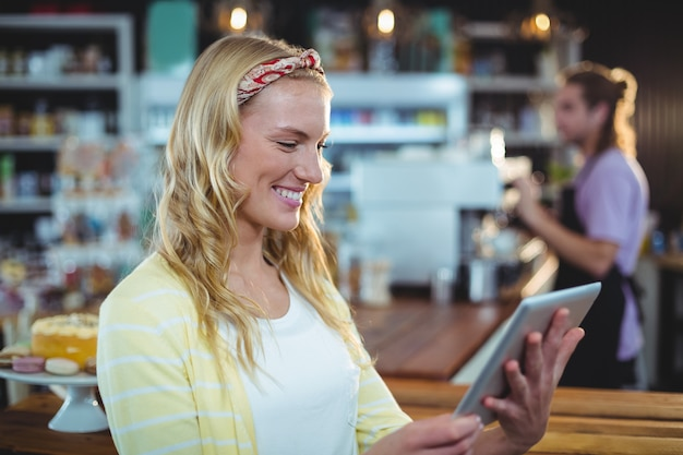 Glimlachende vrouw die digitale tablet gebruiken