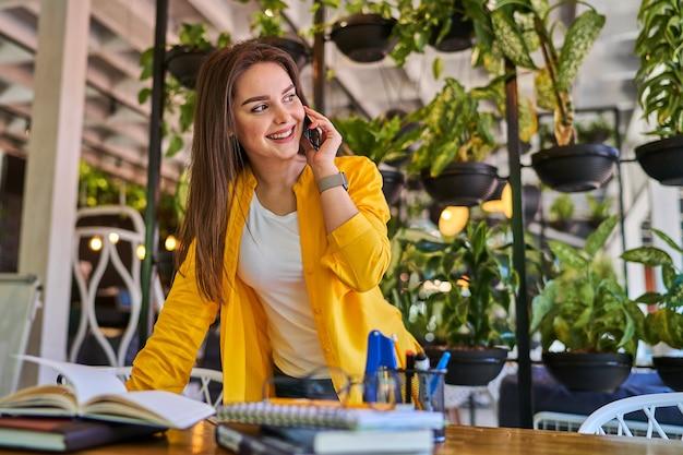 Glimlachende vrouw die door mobiele telefoon in haar bureau spreekt.
