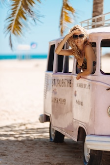 Glimlachende vrouw die door venster van hippieauto kijken op strand
