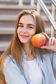 Glimlachende vrouw die een appel dicht bij haar gezicht houdt