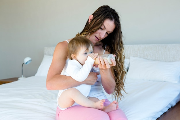 Glimlachende vrouw die een baby in haar slaapkamer met de fles grootbrengt