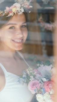 Glimlachende vrouw die een bloemenkrans draagt en een boeket bloemen vasthoudt