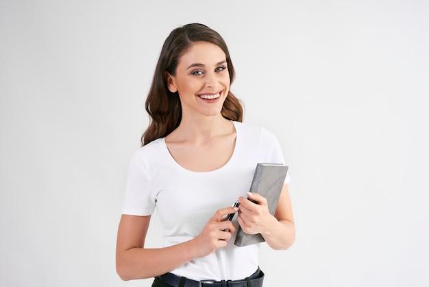 Glimlachende vrouw die een boek houdt