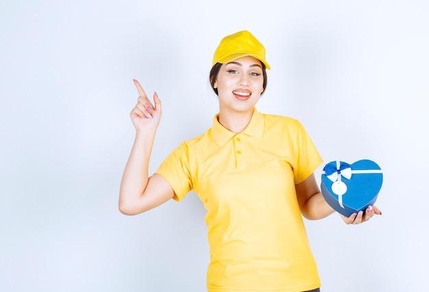 Glimlachende vrouw die een doos vasthoudt en met de vinger in de lucht wijst
