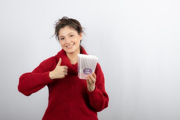 Glimlachende vrouw die een emmer met popcorn houdt en een duim toont.