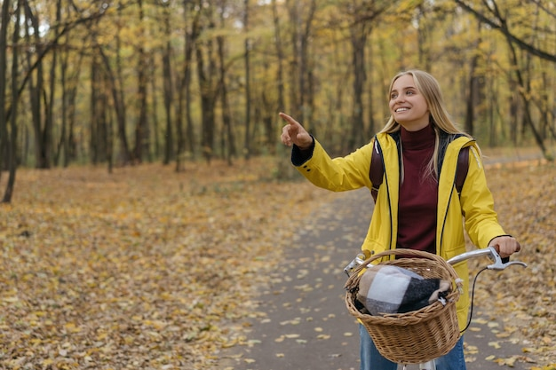 Glimlachende vrouw die een fiets in het park berijdt, die vinger op exemplaarruimte toont
