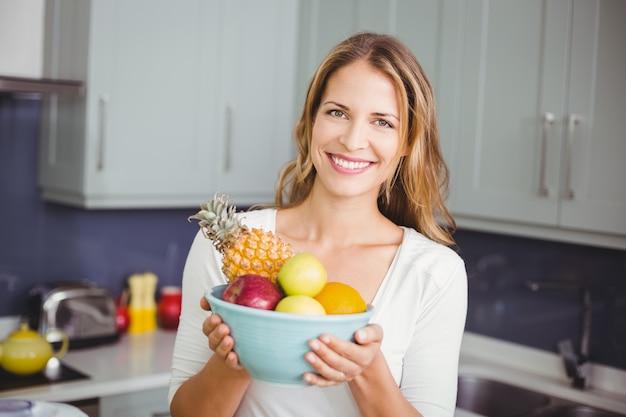 Glimlachende vrouw die een fruitkom houdt