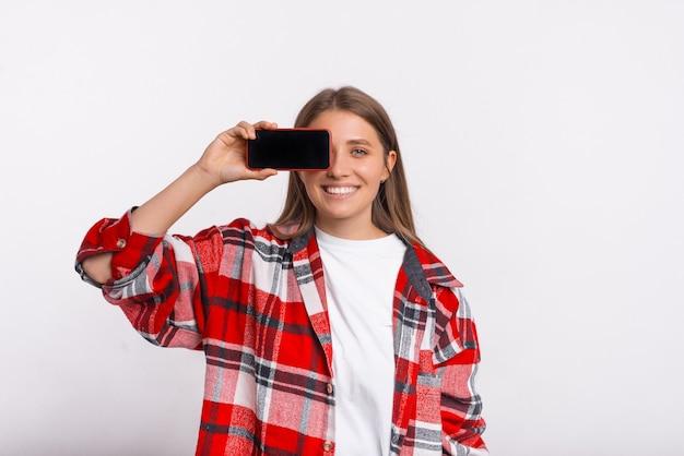 Glimlachende vrouw die een geruit overhemd draagt, bedekt één oog met de telefoon die ze vasthoudt.