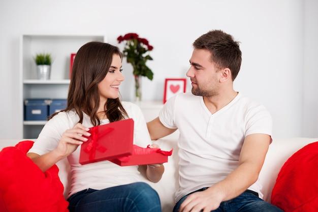 Glimlachende vrouw die een gift van valentijnskaart opent