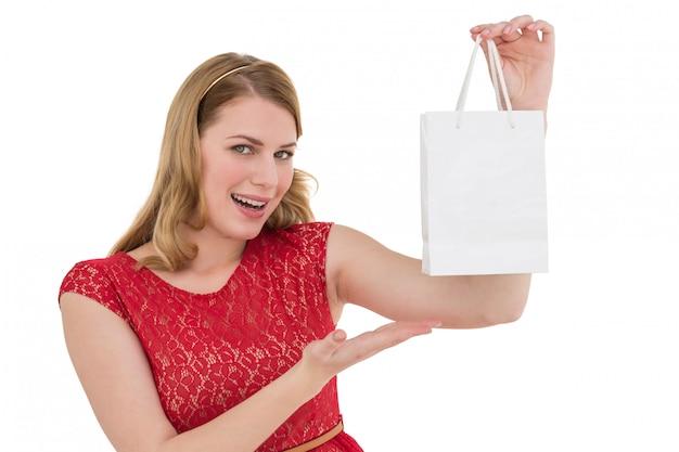 Glimlachende vrouw die een het winkelen zak voorstelt