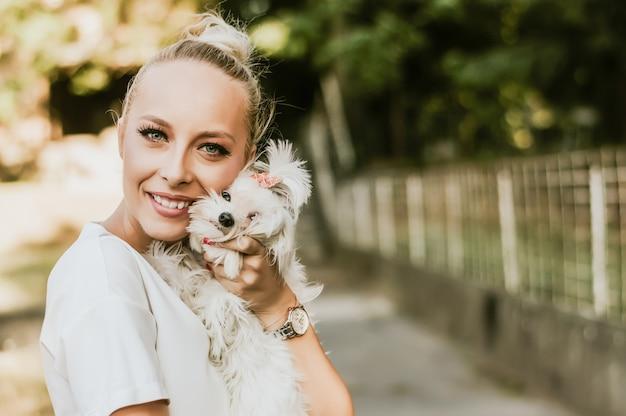 Glimlachende vrouw die een kleine witte maltese hond houdt.