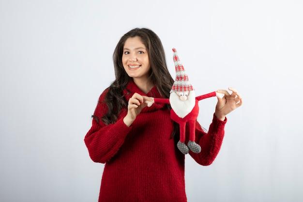 Glimlachende vrouw die een knuffel van de kerstman in haar handen houdt.