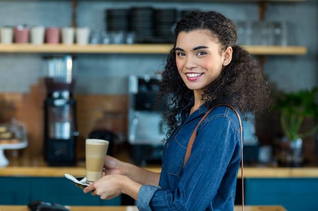 Glimlachende vrouw die een kop van koffie in koffiewinkel houdt