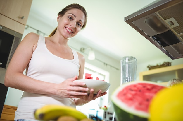 Glimlachende vrouw die een plaat van watermeloen houdt