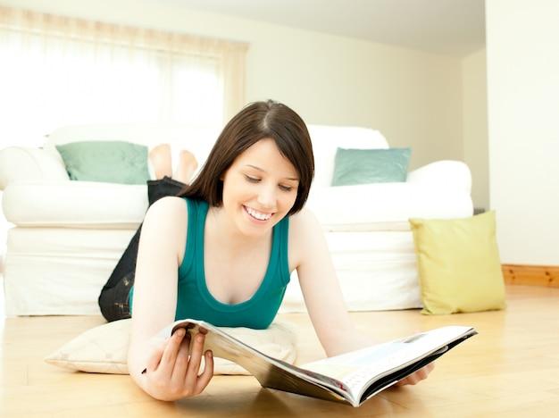 Glimlachende vrouw die een tijdschrift lezen die op de vloer liggen