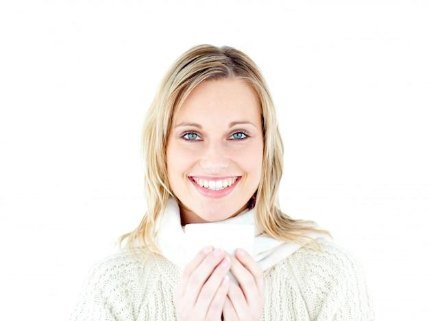 Glimlachende vrouw die een trui draagt die van een hete koffie geniet