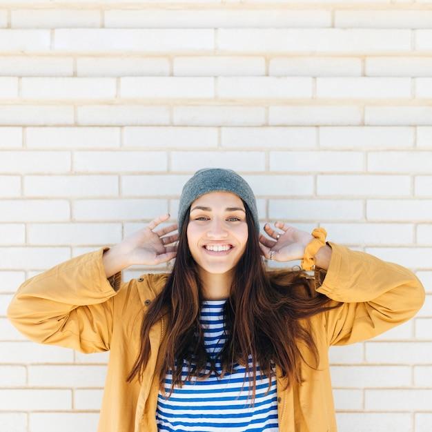Glimlachende vrouw die gebreide hoed en jasje dragen die zich voor bakstenen muur bevinden
