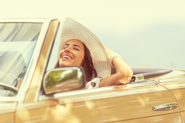 Glimlachende vrouw die geniet van haar zomerse cabriorit die haar hoed met één hand vasthoudt.