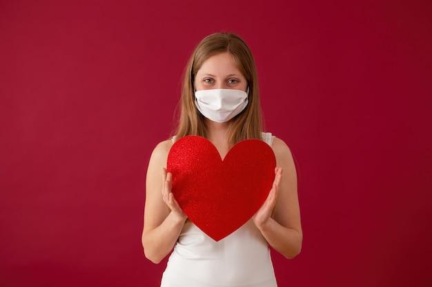 Glimlachende vrouw die gezichtsmasker draagt en rood hart in handen houdt.