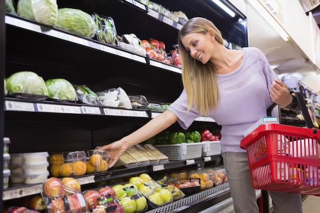 Glimlachende vrouw die groenten in de doorgang nemen