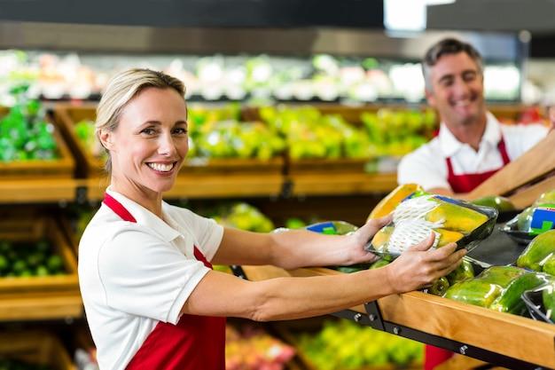 Glimlachende vrouw die groentendoos vullen