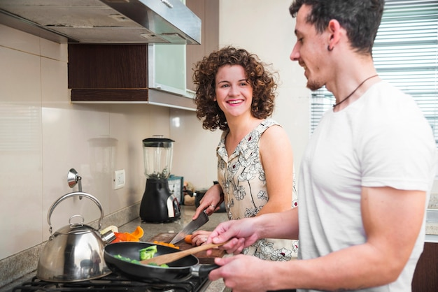Glimlachende vrouw die haar echtgenoot bekijken die voedsel in de keuken voorbereiden